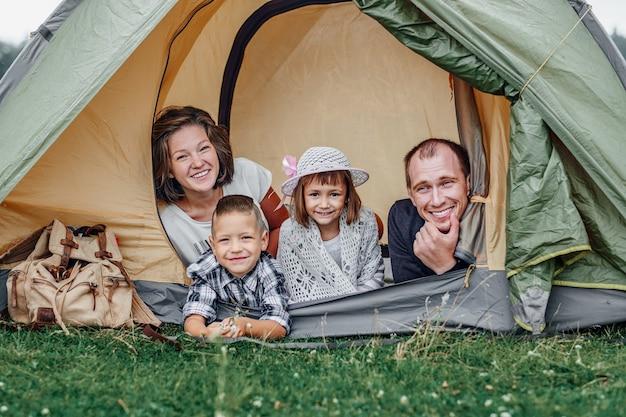 Familie eltern und zwei kinder im lagerzelt. glückliche mutter, vater, sohn und tochter im sommerurlaub.