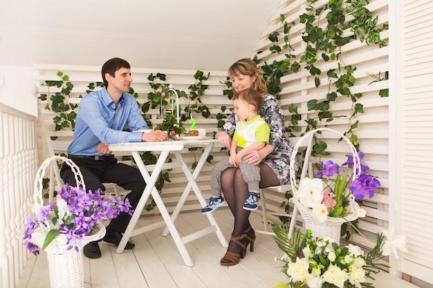 Familie, elternschaft, alles gute zum geburtstag und urlaubskonzept - glückliche eltern und kind an einem tisch, der tee trinkt und kuchen isst.