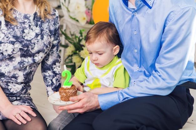 Familie, elternschaft, alles gute zum geburtstag und urlaubskonzept - nahaufnahme glücklicher eltern und kind an einem tisch, der tee trinkt und kuchen isst