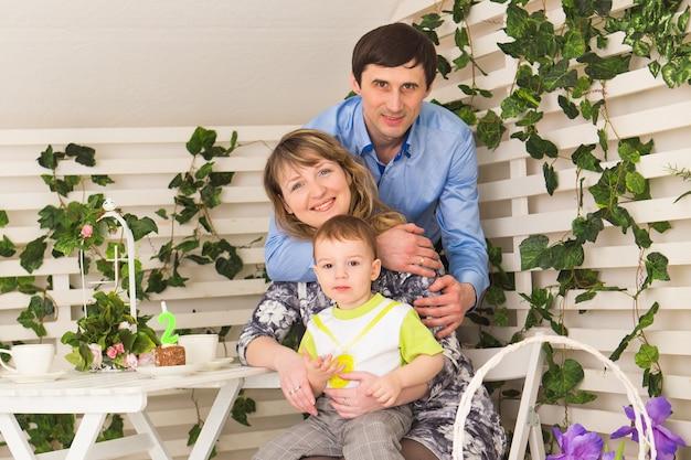 Familie, elternschaft, alles gute zum geburtstag und urlaubskonzept - porträt von glücklichen eltern und kindern an einem tisch, der tee trinkt und kuchen isst.
