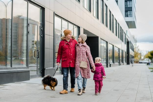 Familie, elternschaft und menschen konzept-glückliche mutter, vater und kleines mädchen gehen in herbststadt und haben spaß.
