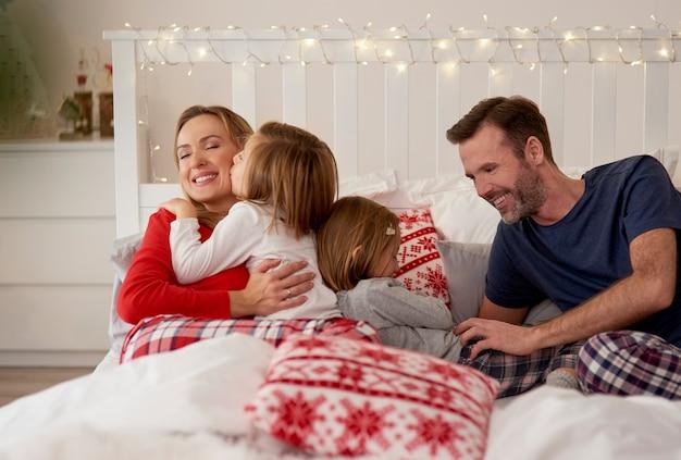 Familie feiert weihnachten im bett