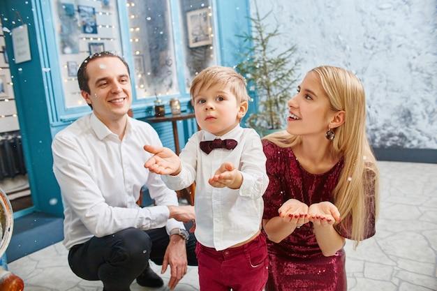 Familie feiert weihnachten und neujahr. mutter, vater und sohn umarmen sich, familienurlaub