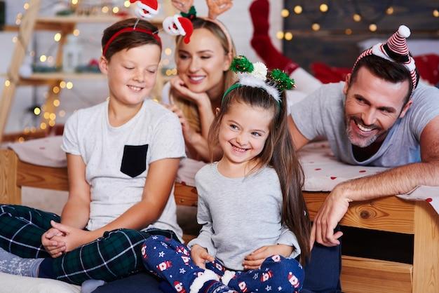 Familie feiert weihnachtsmorgen zusammen im schlafzimmer