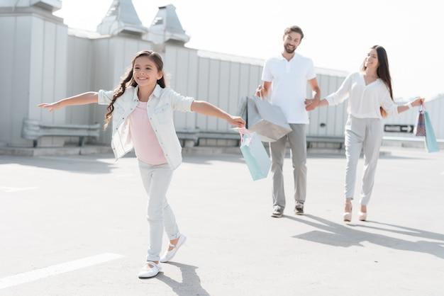 Familie gehen auf dem parkplatz nach dem einkauf im einkaufszentrum