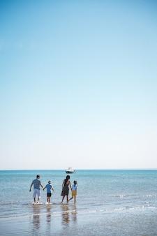 Familie geht auf dem meer spazieren, vier mama, papa, sohn und tochter.