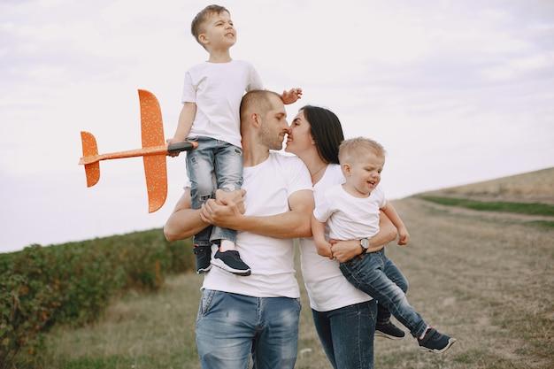 Familie geht in ein feld und spielt mit spielzeugflugzeug