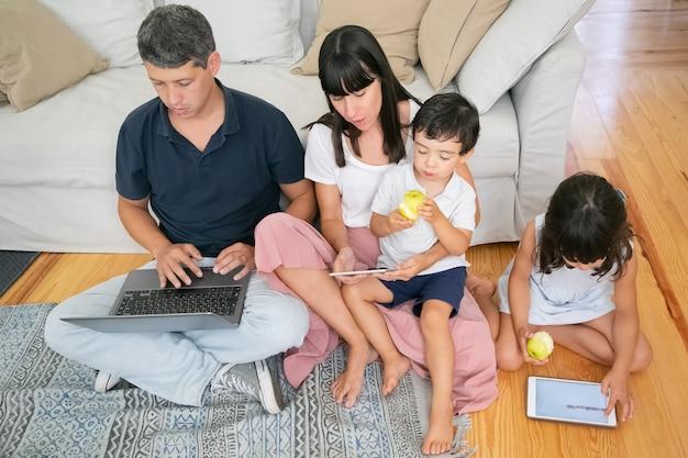 Familie genießt die gemeinsame freizeit, nutzt digitale geräte und isst frische äpfel in der wohnung.