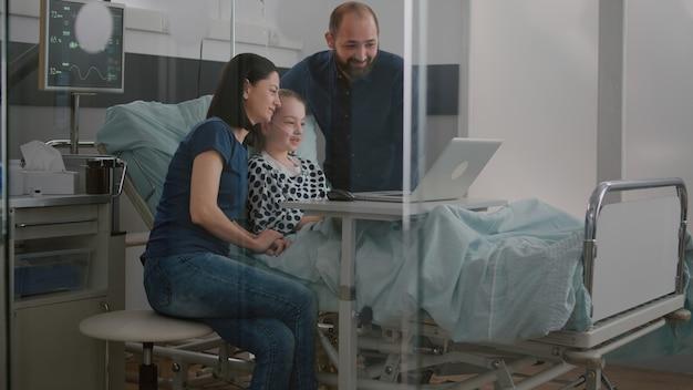 Familie grüßt entfernte freunde während der online-videoanruf-telekommunikation mit laptop-computer in ho...