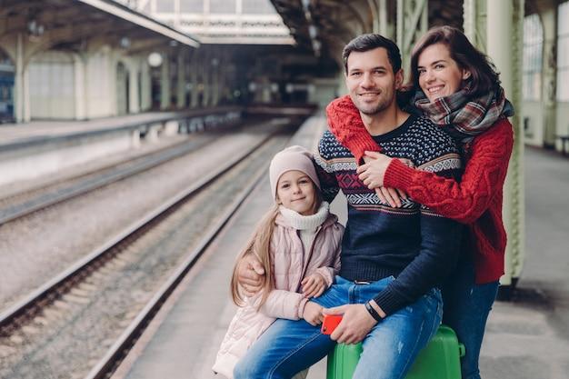 Familie haben gute beziehung, haben reise während des urlaubs, werfen am bahnsteig des bahnhofs auf.
