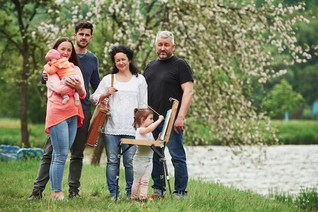 Familie haben gute zeit in der parklandschaft. junger maler, der das zeichnen lehrt