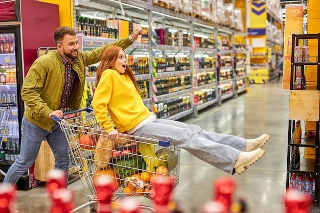 Familie haben spaß im gang des lebensmittelladens, frau sitzt auf wagen und genießt das einkaufen mit ehemann. seitenansicht