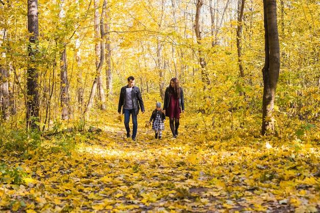 Familie, herbst, menschenkonzept - junge familie, die am herbsttag im park spazieren geht