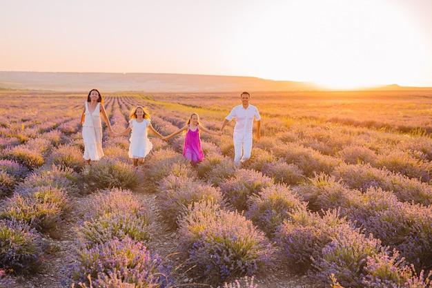 Familie im lavendelblumenfeld auf dem sonnenuntergang