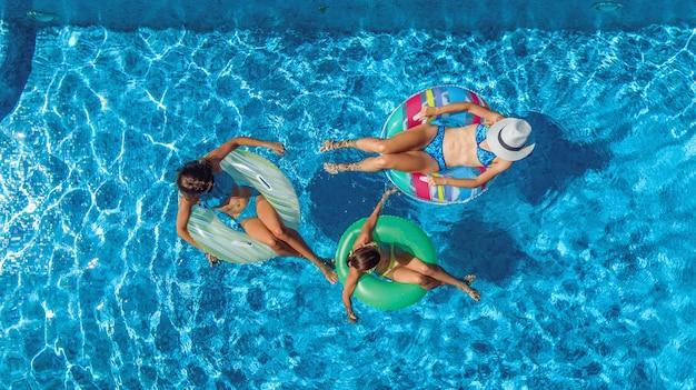 Familie im schwimmbad luftdrohnenansicht von oben, glückliche mutter und kinder schwimmen auf aufblasbaren ringkrapfen und haben spaß im wasser im familienurlaub, tropische ferien im resort