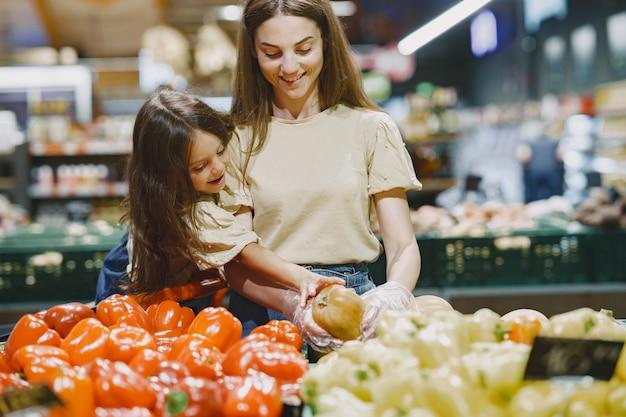 Familie im supermarkt. frau in einem braunen t-shirt. die leute wählen gemüse. mutter mit tochter.