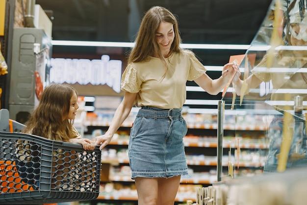 Familie im supermarkt. frau in einem braunen t-shirt. menschen wählen produkte. mutter mit tochter.
