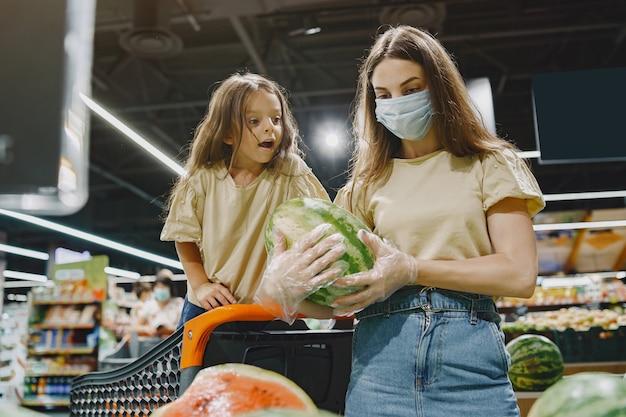 Familie im supermarkt. frau in einer schutzmaske. die leute wählen gemüse. mutter mit tochter. coronavirus.