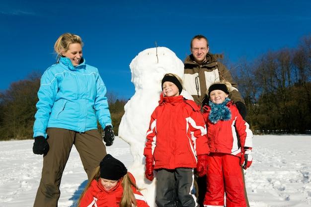 Familie im winter vor ihrem schneemann stehen