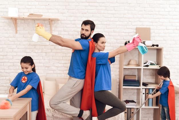 Familie in anzügen von superhelden wirft auf der kamera zu hause auf.
