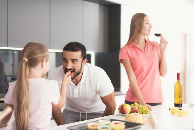 Familie in der küche. das mädchen füttert dem mann eine karotte.