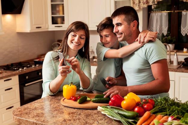 Familie in der küche, die bilder auf smartphone betrachtet