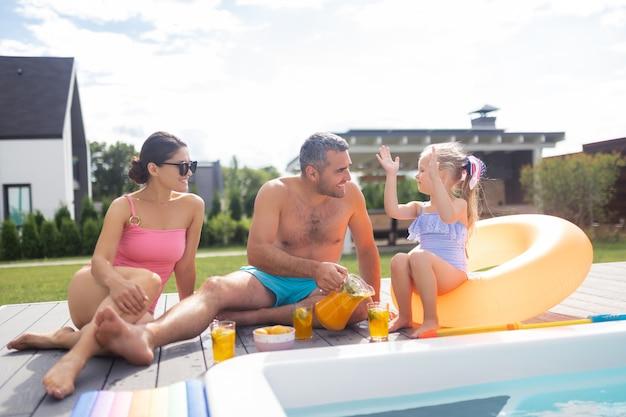 Familie in der nähe des pools. tochter fühlt sich schön, während sie zeit mit den eltern in der nähe des pools verbringt?