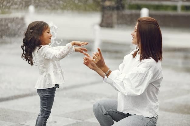 Familie in der nähe des stadtbrunnens. mutter mit lachen spielt mit wasser.