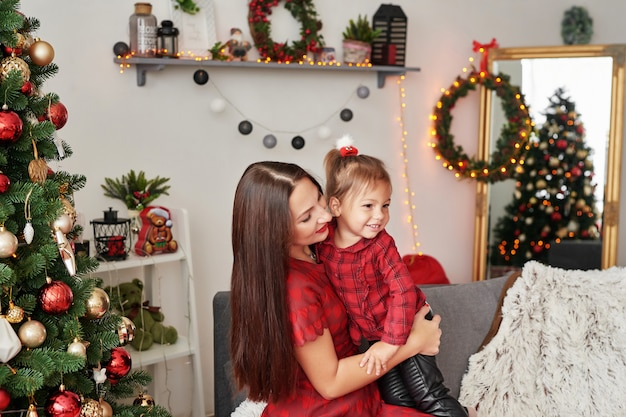 Familie in der nähe von weihnachtsbaum. glückliche familienmutter und -baby nahe weihnachtsbaum im feiertag. frohe weihnachten und schöne feiertage! liebevolle familie mit geschenken im raum.
