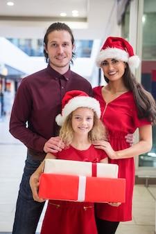 Familie in der weihnachtskleidung, die mit weihnachtsgeschenken steht