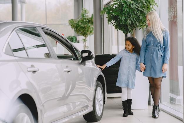Familie in einem autosalon. frau, die das auto kauft. kleines afrikanisches mädchen mit mther.