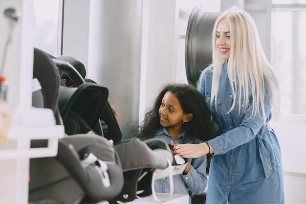 Familie in einem autosalon. frau, die den autositz kauft. kleines afrikanisches mädchen mit mther.