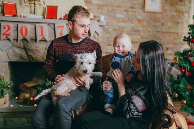 Familie in einem einzigen sessel sitzt mit ihrem hund und ihr baby
