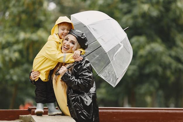 Familie in einem regnerischen park. kind in einem gelben regenmantel und frau in einem schwarzen mantel.