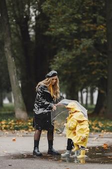 Familie in einem regnerischen park. kinder in gelben regenmänteln und frau in schwarzem mantel.