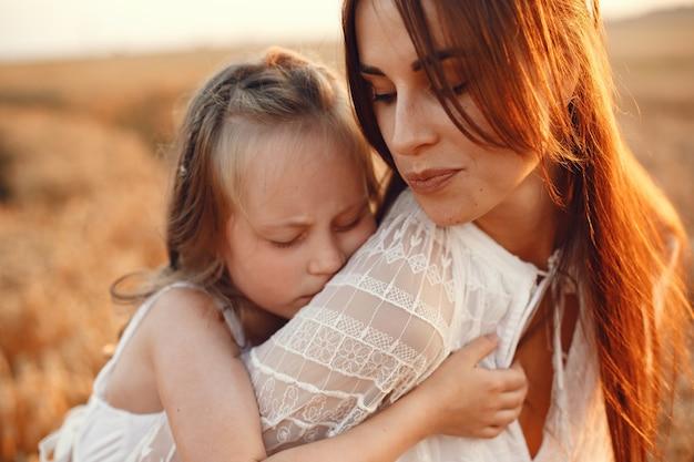 Familie in einem sommerfeld. sinnliches foto. süßes kleines mädchen. frau in einem weißen kleid.