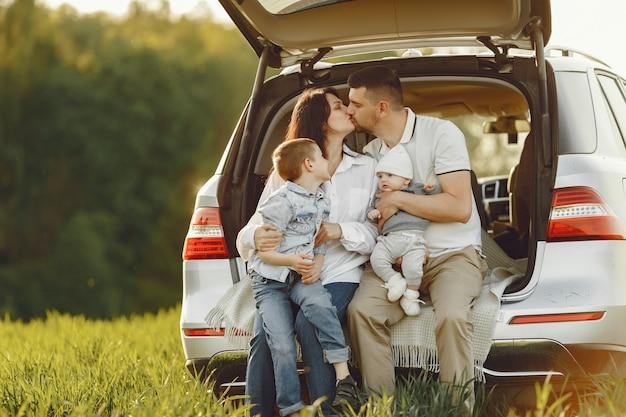 Familie in einem sommerwald am offenen stamm