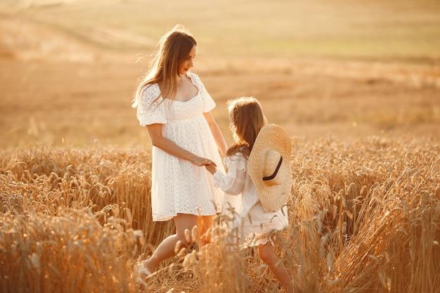 Familie in einem weizenfeld. frau in einem weißen kleid. mädchen mit strohhut.