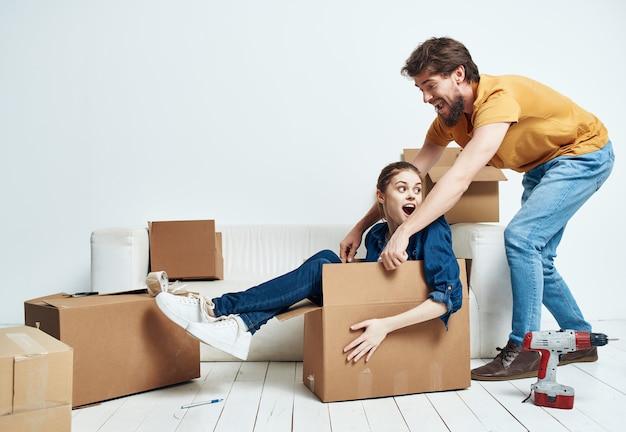Familie in einer neuen wohnung kartons mit sachen werkzeuge auspacken