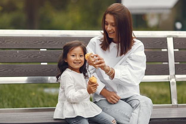 Familie in einer stadt. kleines mädchen isst eis. mutter mit tochter sitzt auf einer bank.