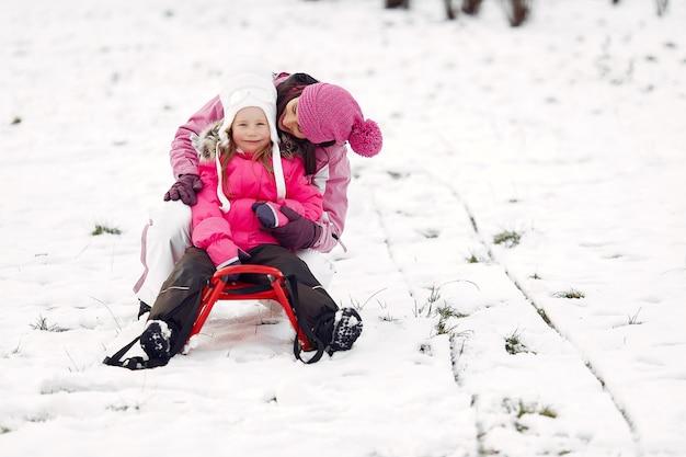 Familie in gestrickten wintermützen auf familienweihnachtsferien. frau und kleines mädchen in einem park. leute, die mit schlitten spielen.