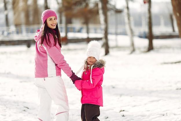 Familie in gestrickten wintermützen auf familienweihnachtsferien. frau und kleines mädchen in einem park. leute spielen.