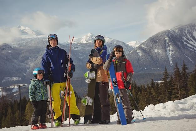 Familie in skibekleidung, die zusammen auf schneebedeckten alpen steht