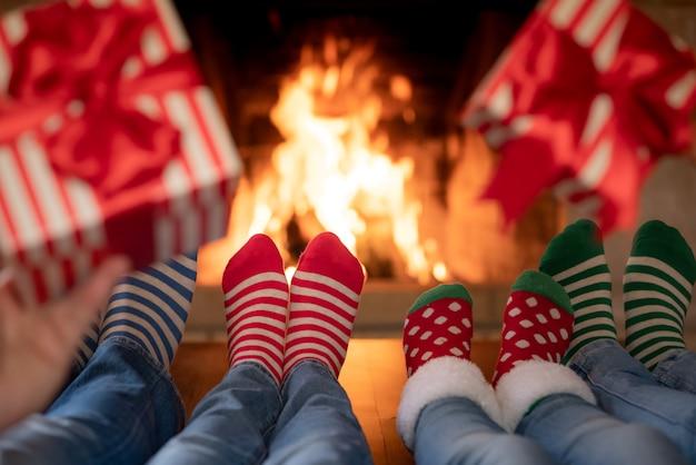 Familie in weihnachtssocken in der nähe des kamins muttervater und kinder, die zusammen spaß haben