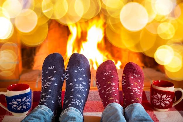 Familie in weihnachtssocken in der nähe von kamin. mutter; vater und baby haben spaß zusammen. menschen, die sich zu hause entspannen