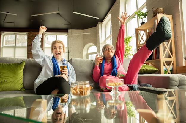 Familie jubelt und sieht zu hause im wohnzimmer fern