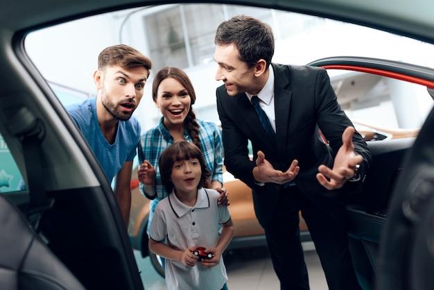 Familie kam zum autosalon, um ein neues auto zu wählen.