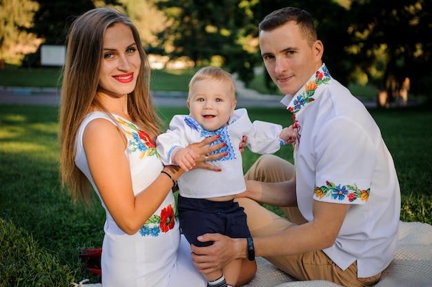 Familie kleidete in den traditionellen gestickten hemden an, die auf dem plaid im park sitzen