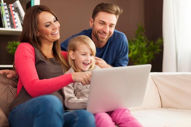 Familie lacht zusammen und benutzt laptop zu hause