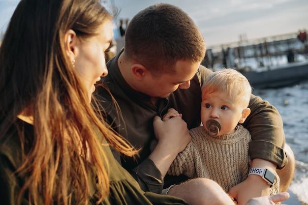Familie. mama, papa und baby, die am kai sitzen, eltern, die zu ihrem sohn schauen, der einen schnuller lutscht. bild mit selektivem fokus. foto in hoher qualität